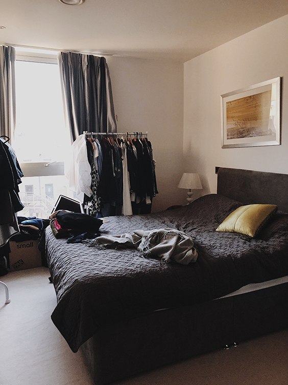 small bedroom with black bed and coat racks in westminster, London