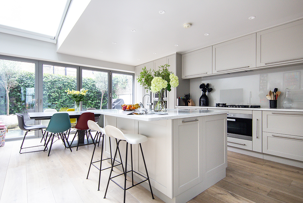 grand and spacious interior design for kitchen with large dining area,bespoke joinery and bright chairs in Chelsea, London