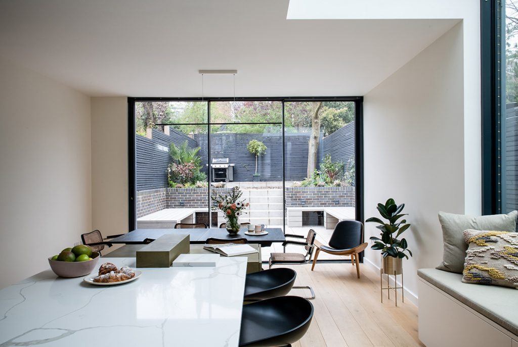 interior design for light and spacious kitchen with dining area and floor to ceiling glass doors in Bromley, London