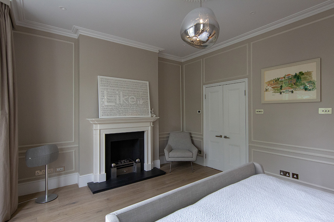 residential interior design for spacious bedroom with grey painted walls, comfy bed, fireplace, wooden flooring and grey armchair, Chelsea, London