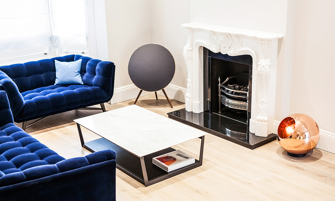 residential interior design for spacious light living room with white fireplace, wooden coffee table, comfy blue velvet armchairs, London