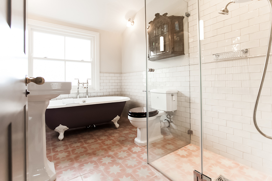 grand and spacious interior design for a traditional bathroom in Victorian style with beatiful tiled flooring, free standing bath on the feet, shower stall in Shepherds Bush, London