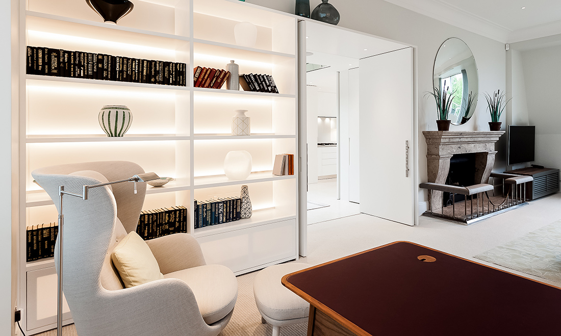 residential interior design for a spacious open plam livingroom and home office with comfy white armchair, bespoke bookshelf with recessed lighting, Chelsea, London