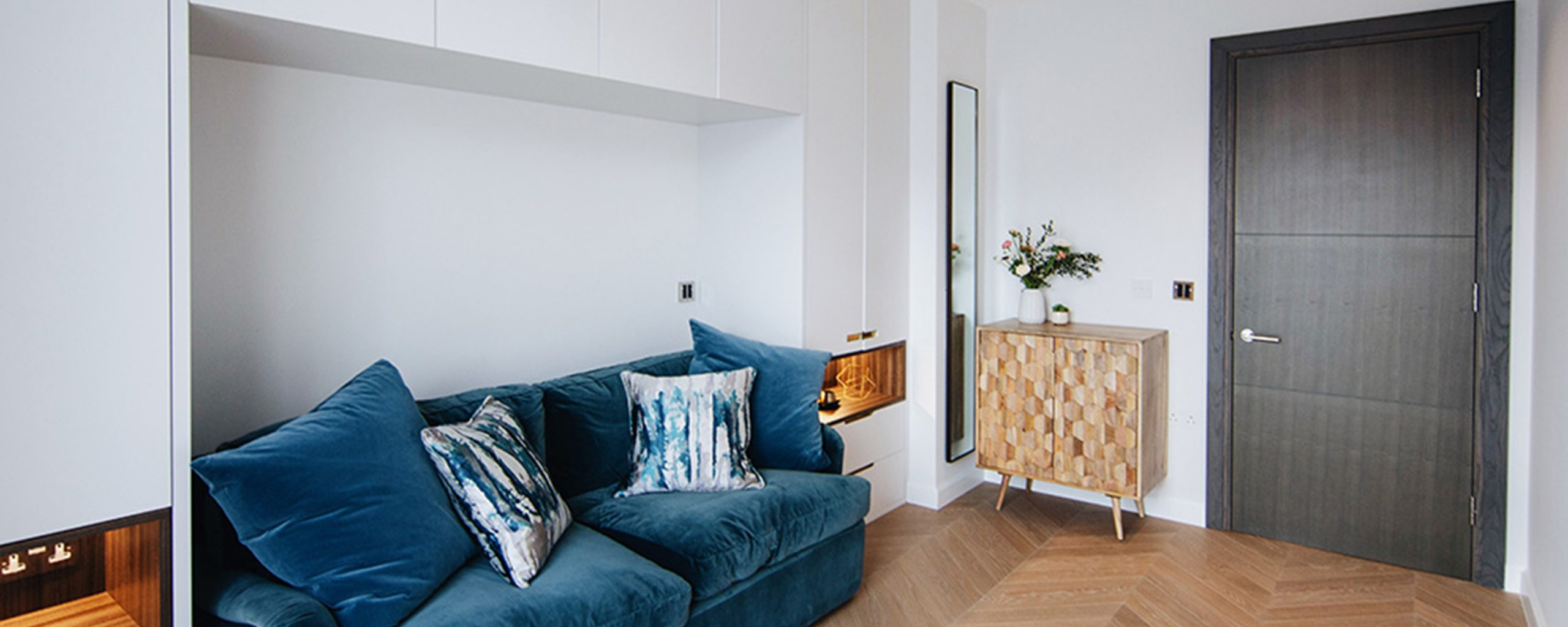 smart storage solutions for small yet practical living room with white bespoke joinery, blue cosy sofa, Westminster, London