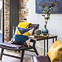 picture of residential interior design for open plan living room and kitchen in eclectic style with designer leather chairs and bright blue and yellow cusions in bentworth road london