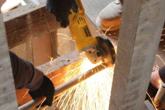 picture of a construction worker cutting pipe using an angle grinder